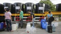 People queue for water in Caracas