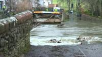 Bridge washed away by flooding in Cumbria