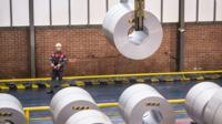 A steelworker moving steel coils