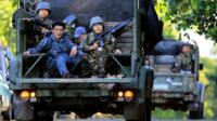 Government soldiers on military vehicles patrol after a continued assault on fighters from the Maute group who have taken over large parts of Marawi city
