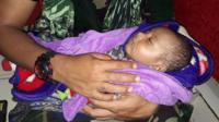 A five-month-old boy has been rescued in Indonesia's flash floods
