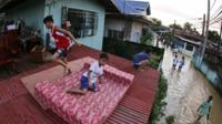 Filipino villagers take refuge on a roof of a house at a flooded village of Calumpit, Bulacan province, northern Philippines