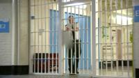 Prison officer seen through railings locking prison door.