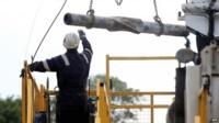 A worker moves drilling equipment at the exploratory drilling site operated by British energy firm Cuadrilla in the village of Balcombe, southern England