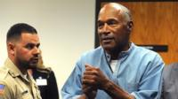OJ Simpson (L) reacts after being granted parole at Lovelock Correctional Centre in Lovelock