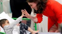 The Duchess of Cambridge and a child.