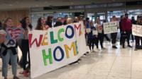 People stand with banners in Dublin airport