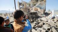 A boy uses a cell phone to take photos of the wreckage of a house destroyed by a Saudi-led air strike on the outskirts of Sanaa, Yemen
