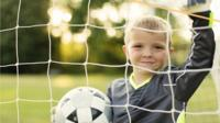 Boy with football in goal