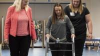 Kelly Thomas uses a frame to walk