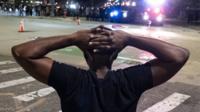 Black man under arrest with hands on head