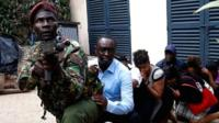Kenyan police special forces man with red beret and gun, with civilians behind him