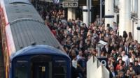 File photo dated 30/04/14 of commuters using overground train services waiting to pass through the barriers at Waterloo station, London, during strike by tube workers
