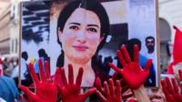 Image of Hevrin Khalaf held up during a protest with people showing hands covered in red paint