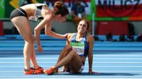 Nikki Hamblin (NZ) helping up Abbey D'Agostino (US) after joint crash on the track