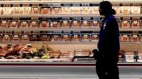 """A employee walks by a meat cooler in the grocery section of a Sam""""s Club during a media tour in Bentonville, Arkansas, U.S. on June 5, 2014"""