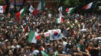 Ecstatic Mexico fans wave the flag of South Korea