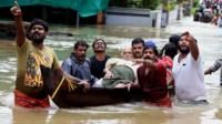 Indian people use a boat to rescue an elderly man in the flooded water in Kochi, Kerala state, India, 17 August 2018