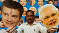 A shopkeeper poses with masks of Congress party leader Rahul Gandhi and Indian Prime Minister Narendra Modi