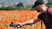 Photographer in field of poppies
