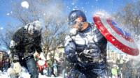 Jeff Dacanay (C), while dressed as Captain America, is pelted with snow during a snowball fight following a blizzard, at Dupont Circle in Washington, DC