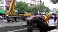 Crane pulls car out of hole