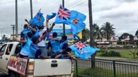 Men in the back of a pickup truck in Fiji T-shirts and waving Fiji flags