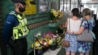 A Police Community Support Officer stands as people stop to look at floral tributes left at Aldgate underground station, London