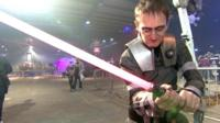 A man wearing a Star Wars outfit wields a toy light sabre