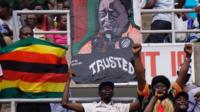 Supporters hold a portrait of Zimbabwe's new President Emmerson Mnangagwa on 24 Nov