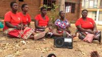 Women in a village listening to a radio.