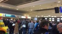 Passengers are left in long queues at Belfast International Airport after flights were cancelled because of a freight plane stuck on a runway.