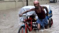 An Indian labourer pushes his cycle trishaw through floodwaters in Chennai
