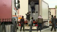 A group of migrants trying to climb into the back of a lorry in Calais