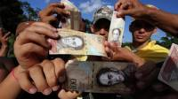 People hold up the 100-bolivar note