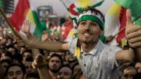 A supporter stands out form the throng, lifted on other's shoulders in a large crowd waving the Kurdish region's flag earlier this week
