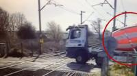 Railway crossing barrier closing on lorry