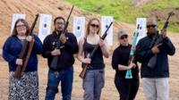 Five people from minority groups holding rifles, standing in front of targets at a shooting range in San Diego.
