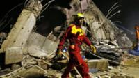 Rescuers remove debris as they continue to search for survivors