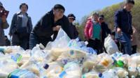 Activists in South Korea pack bottles with food and medicine to send to their neighbours in the North