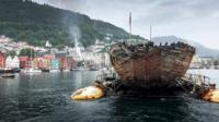 The hull of the Maud is seen in the water in front of a Nordic coastal town
