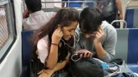 A couple watching and listening to video on a mobile phone