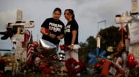 Heather Mesch (C) and her daughter Alexa place roses next to crosses placed in front of the fence of the Marjory Stoneman Douglas High School to commemorate the victims of the mass shooting, in Parkland, Florida, U.S., February 21, 2018