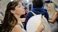 Woman with fan on tube in London