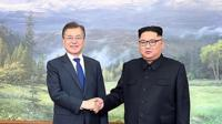 Moon Jae-in shakes hands with Kim Jong-un