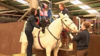 Olivia Fairclough being lifted on to a horse