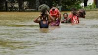 Sri Lankan residents make their way through floodwaters in Kaduwela on May 27, 2017. Rainfall on May 26 triggered the worst flooding and landslides in 14 years in the southern and western parts of Sri Lanka, authorities said. The Disaster Management Centre (DMC) said 103 people were confirmed killed while another 113 were missing. / AFP PHOTO / ISHARA S. KODIKARA (Photo credit should read ISHARA S. KODIKARA/AFP/Getty Images)