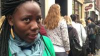 Woman speaking in front of queue