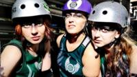 Three roller derby skaters look