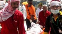 Saudi emergency personnel and Hajj pilgrims carry a wounded person
